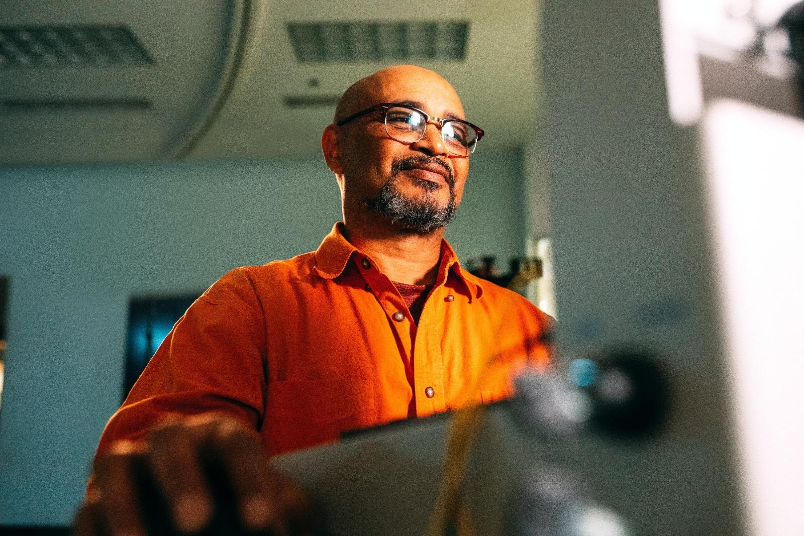 guy in orange shirt in front of computer